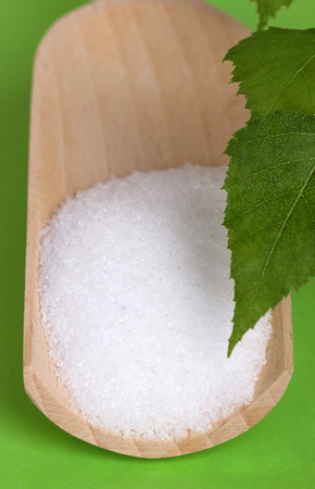 edible plant: Xylitol birch sugar on wooden scoop with birch leaves over green. White granulated sugar alcohol, substitute used as sweetener that taste like table sugar, extracted from the wood of birch trees.