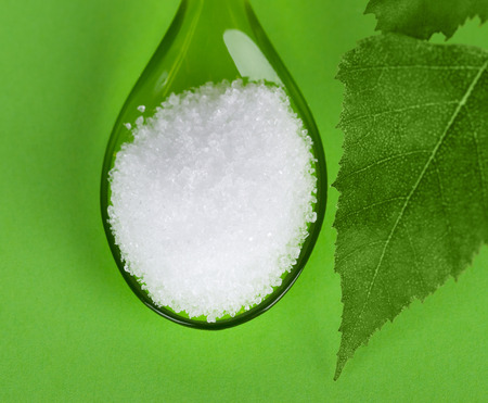 surrogate: Xylitol birch sugar on plastic spoon with birch leaves on green background. White granulated sugar alcohol substitute used as sweetener that taste like table sugar, extracted from wood of birch trees.