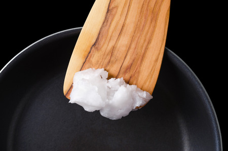 copra: Coconut oil on wooden spatula over coated pan. Also copra oil, an edible oil, extracted from the kernel of meat of mature coconuts harvested from the coconut palm, Cocos nucifera. Macro food photo.