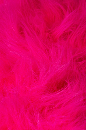 long hairs: Pink plush fabric vertical. Very soft polyester textile made of synthetic fibers with long hairs. Macro close up material photography.