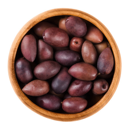 close up food: Kalamata black olives in a wooden bowl over white. Greek large purple table olives. A variety grown elsewhere are called Kalamon olives. Dried ripe fruits of Olea europaea. Macro close up food photo.
