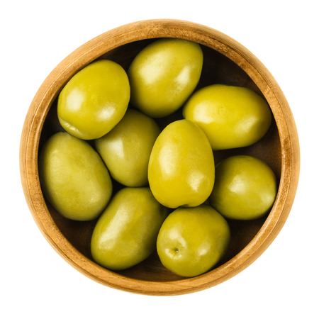 extra large: Gordal Reina green olives in a wooden bowl over white. The Queen of all olives. Extra large and very succulent table olives from Andalusia, Spain. Dried ripe fruits of Olea europaea. Macro food photo.