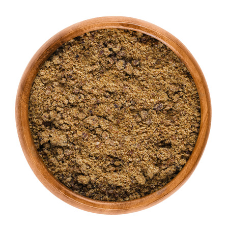 unrefined: Muscovado dark brown sugar in a bowl over white. Also called Khaand, unrefined non-centrifugal cane sugar with strong molasses content and flavor from the Philippines, used in baking and making rum.