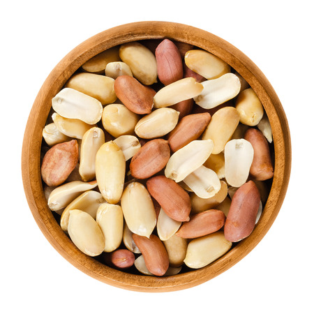 goober: Shelled peanuts in wooden bowl on white background. Dry roasted Arachis hypogaea, also called groundnut and goober, used as a snack. Isolated macro food photo close up from above. Stock Photo