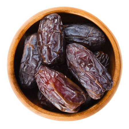 dactylifera: Dried Medjool dates from Morocco in a wooden bowl on white background, also called Mejhool. Large, sweet and succulent fruits of date palms, Phoenix dactylifera. Isolated macro food photo close up.