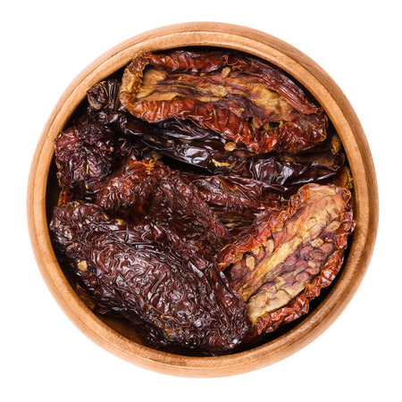 Sun dried tomatoes in wooden bowl on white background. Ripe tomatoes lost most of their water after drying in the sun, treated with salt for preservation. Isolated macro food photo close up.