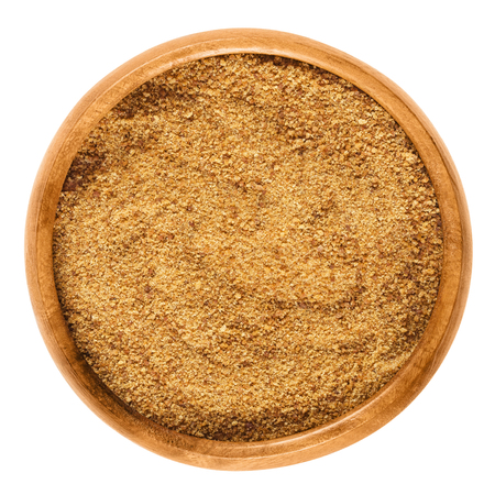 Dark coconut blossom sugar in a wooden bowl on white background. Raw brown unrefined sugar from the coconut palm, an edible, organic and vegan sweetener. Isolated macro food photo close up from above. Stockfoto
