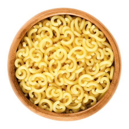 helical: Gobbetti pasta in wooden bowl. Italian noddles, short-cut and G-shaped helical bent tubes. Uncooked dried durum wheat semolina pasta. Isolated macro food photo over white background. Stock Photo