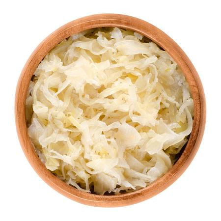 白椀でドイツのザワークラウト。長い貯蔵寿命とおかずとして使用、独特の甘酸っぱい風味の乳酸菌で発酵させたキャベツを細かくカットします。孤立したマクロ料理写真。 写真素材