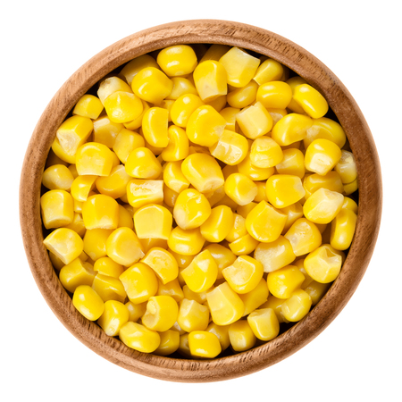 zea mays: Sweet corn kernels in wooden bowl over white. Cooked canned yellow vegetable maize, Zea mays, also called sugar or pole corn, a vegetarian staple food. Isolated macro food photo close up from above. Stock Photo