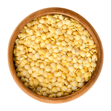 pulses: Yellow lentils in wooden bowl on white background. Seeds of Lens culinaris, edible raw pulses of the legume family. Isolated close up macro food photo from above. Stock Photo