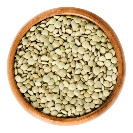 pulses: Green lentils in wooden bowl on white background. Seeds of Lens culinaris, edible raw pulses of the legume family. Isolated close up macro food photo from above. Stock Photo