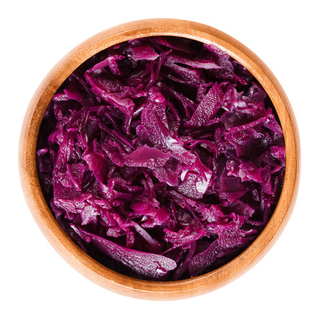 red cooked: Cooked red cabbage in wooden bowl. Brassica oleracea, also purple cabbage, red or blue kraut. Used as a side dish for German meals. Isolated macro food photo close up from above on white background. Stock Photo
