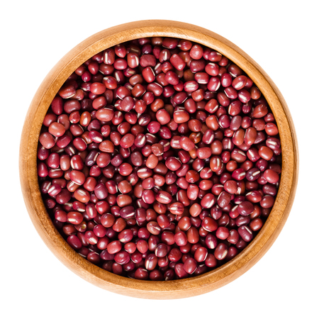 angularis: Red adzuki beans in wooden bowl, also called azuki, aduki or Red Mung Bean. Dried small beans of Vigna angularis. Isolated macro food photo close up from above on white background. Stock Photo