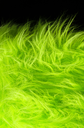 black hairs: Yellow green fabric on black background vertical. Very soft polyester textile made of synthetic fibers with long hairs. Macro close up material photography, front view. Stock Photo