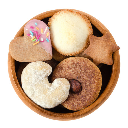 sweet heart: Cookies and biscuits in wooden bowl. Assorted flat sweet baked goods in heart, crescent, star and disc shapes with different decor. Isolated macro food photo close up from above on white background.