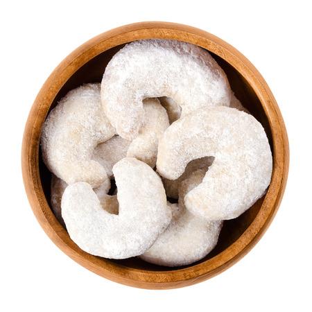 galletas: De media luna en forma de galletas de vainilla en un tazón de madera. Vainilla lunas de almendras o medio Vanillekipferl, una galleta de la navidad scecialty de Austria. Aislado de macro fotografía de cerca desde arriba sobre fondo blanco.