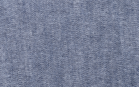 weave: Blue denim textile. Surface of sturdy cotton warp-faced fabric. Twill, type of textile weave with pattern of diagonal parallel ribs. Warp thread is dyed indigo, weft thread is left white. Macro photo. Stock Photo