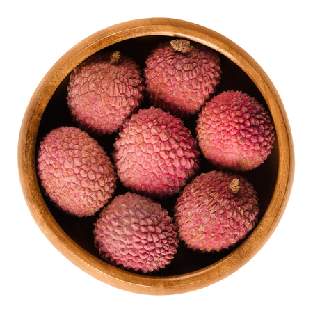 lichee: Lychee or litchi fruits in wooden bowl. Unpeeled ripe red Litchi chinensis, also called liechee, liche, lizhi or li zhi. Isolated macro food photo close up from above on white background. Stock Photo