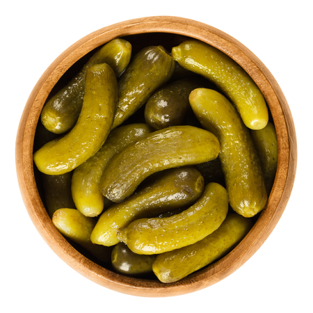 Cornichons, pickled cucumbers in wooden bowl. Green tart French pickles, made from small gherkins. Gherkin, commonly known as pickle. Isolated macro food photo close up from above on white background. Standard-Bild