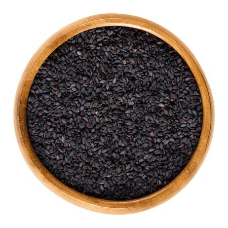 ajonjoli: Semillas de sésamo negro en un tazón de madera. Frutos de Sesamum radiado, también benniseed negro o de sésamo vegetal, se come toda o como pasta. aislado de los alimentos de macro fotografía de cerca desde arriba sobre fondo blanco.