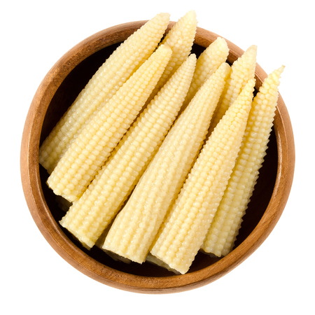 mazorca de maiz: Pickled whole baby corn in wooden bowl. Preserved small cooked corn with bright yellow color in a solution of vinegar and salt. Isolated macro food photo close up from above on white background. Foto de archivo