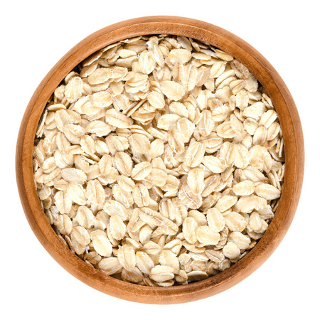hulled: Oatmeal, rolled oats in wooden bowl. Dehusked, hulled oats, rolled into large whole flakes. Porridge oats, used in granola or muesli. Isolated macro food photo close up from above on white background.