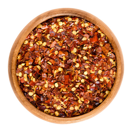 Dried chili pepper flakes in wooden bowl. Dried and crushed fruits of Capsicum frutescens, used as hot spice and for tabasco sauce. Isolated macro food photo close up from above on white background. Stock Photo