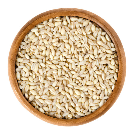 edible plant: Processed pearl barley in wooden bowl. Uncooked pearled barley without hull and bran. Hordeum vulgare, a major cereal grain. Isolated macro food photo close up from above on white background. Stock Photo