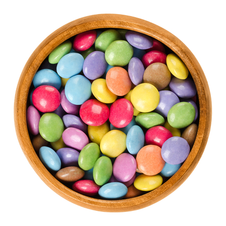 sweetie: Colorful chocolate candies in wooden bowl. Sugar-coated chocolate confectionery in eight different colors. Oblate spheroid shaped candies. Macro food photo close up from above on white background. Stock Photo