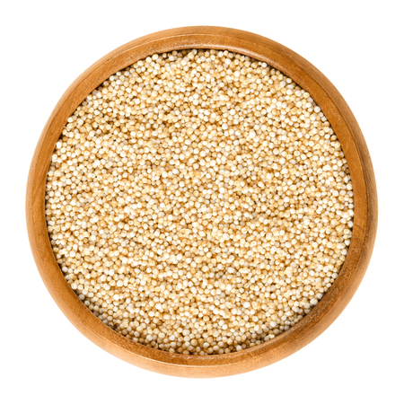 Puffed amaranth in wooden bowl. Popped grains of Amaranthus. Pseudocereal and rediscovered healthy staple food of the Aztec. Breakfast cereal. Isolated macro food photo close up from above over white. Banco de Imagens