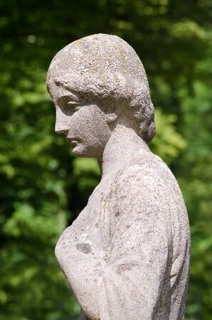 Old stone statue of a woman in sunshine. Her left hand at the bosom, she looks thoughtful, sad, depressed or lonely. Antique weathered sculpture profile in a light flooded park. Photo.