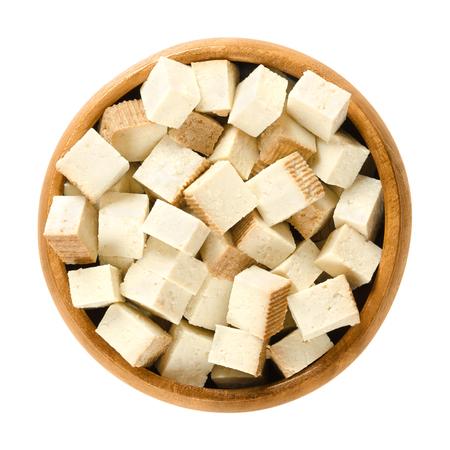Geräucherte Tofuwürfel in Holzschale. Bohnenquark Koagulierte Sojamilch, zu festen weißen Blöcken gepresst. Bestandteil der asiatischen Küche. Fleischersatz Getrennter Makronahrungsmittelfotoabschluß oben von oben über Weiß