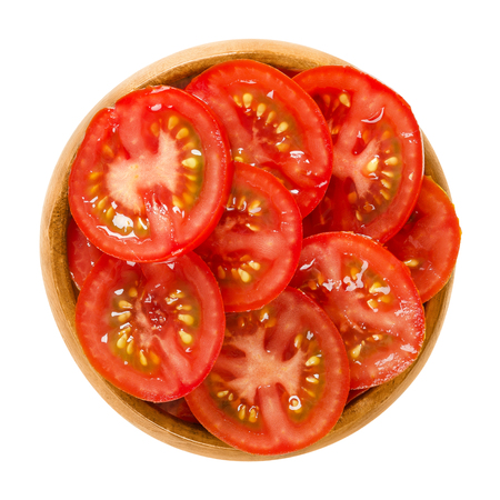 Tomato slices in wooden bowl. Edible ripe and raw fruit of Solanum lycopersicum with red color, cut into thin slivers. Isolated macro food photo close up from above on white background.