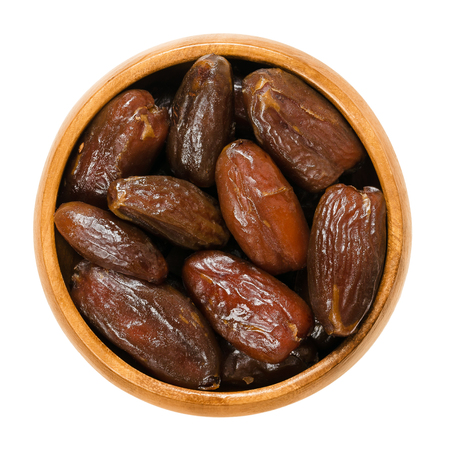 Dried Deglet Nour dates in wooden bowl. Also Deglet Noor, queen of all dates with translucent color. Algerian cultivar of Phoenix dactylifera. Isolated macro food photo close up from above over white.