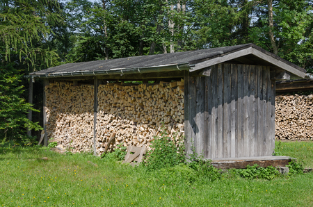Weathered wooden shed with stacked firewood in a meadow on the edge of a forest. Simple roofed structure, used to protect firewood from moisture. Wood construction. Heuberg, Salzburg, Austria. Photo.