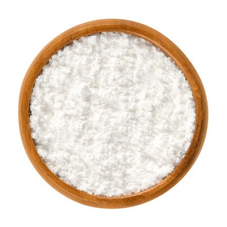 나무 보 울에서 가루 설탕입니다. 변치 않는 흰색 정제 된 설탕. 또한 과자 장수 또는 설탕과 착빙 케이크 장식하기. 격리 된 매크로 음식 사진 위에서