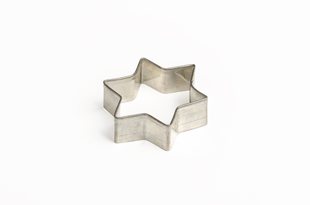 Star shaped Christmas cookie cutter over white. Tin biscuit cutter, a tool to cut cookie dough in particular shape and to make cutouts. Hexagram shaped and six pointed geometric star figure. Photo. Stock Photo