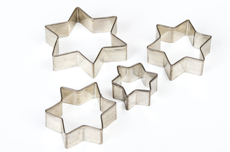 Four star shaped Christmas cookie cutters over white. Tin biscuit cutters, tool to cut cookie dough in particular shapes and to make cutouts. Hexagram shaped and six pointed geometric star figures. Stock Photo