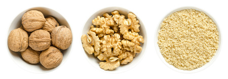 Whole walnuts, kernel halves and ground walnuts in white bowls on white background. Seeds of the common walnut tree Juglans regia, used as snack or for baking. Macro food photo close up from above. Stockfoto