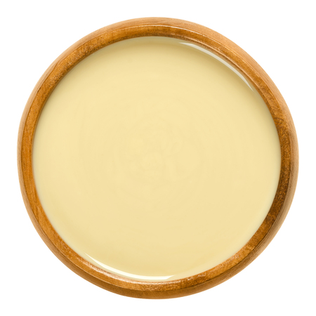 木製のボウルにホワイトアーモンドバター。シェルドブランチアーモンドで作られた滑らかな食品ペースト。プルヌス・ダルシスのナッツのファイ 写真素材