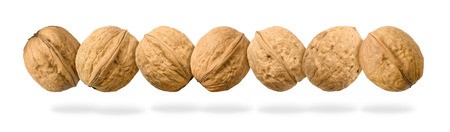 Seven whole walnuts in a row levitating on white background. Stock Photo