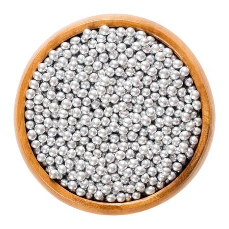 Silver nonpareils in wooden bowl. Hundreds and thousands. Decorative confectionery of tiny balls, made with sugar and starch, used for decoration. Macro food photo close up from above over white.