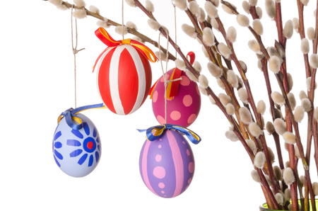Easter eggs on willow bouquet with catkins, horizontal. Four hand-painted colored Paschal eggs on branches of sallows or also called osiers, with aments. Photo on white background.