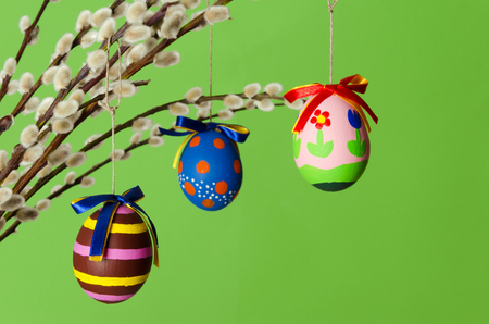 Three colored easter eggs on willow bouquet with pussy willows. Religious decoration. Paschal eggs on branches with furry catkins in vase. Salix. Front view, horizontal, on green background. Photo. Standard-Bild