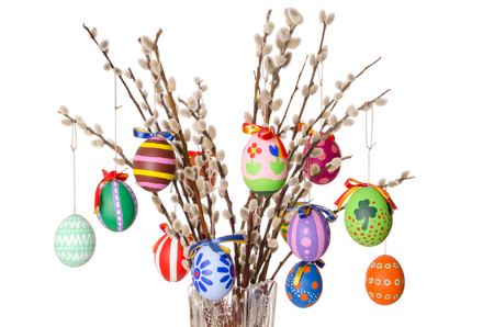 Colored easter eggs on willow bouquet with pussy willows. Religious decoration. Paschal eggs on branches with furry catkins in crystal vase. Salix. Front view, horizontal, on white background. Photo. Imagens - 94753943