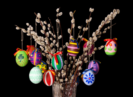 Gekleurde paaseieren op wilgenboeket met pussy wilgen. Religieuze decoratie. Paschalis eieren op takken met harige katjes in kristallen vaas. Salix. Vooraanzicht, horizontaal, op zwarte achtergrond. Foto.