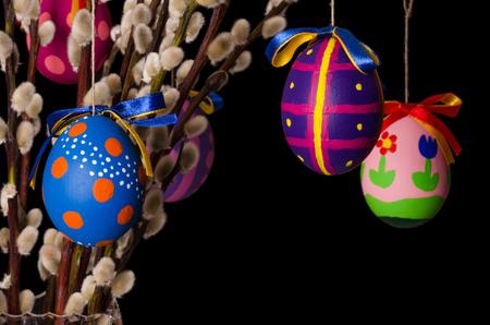 Drie gekleurde paaseieren op wilgenboeket met pussy wilgen. Religieuze decoratie. Paschalis eieren op takken met harige katjes in een vaas. Salix. Vooraanzicht, horizontaal, op zwarte achtergrond. Foto.
