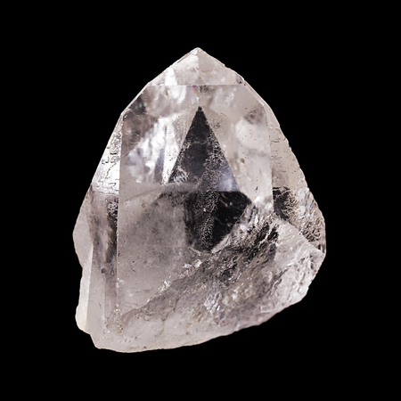 Rough quartz crystal on black background. With pyramid shaped optical illusion inside the mineral. Semi precious gemstone. Silica, silicon dioxide. SiO2. Front view, closeup, isolated macro photo. Stock Photo