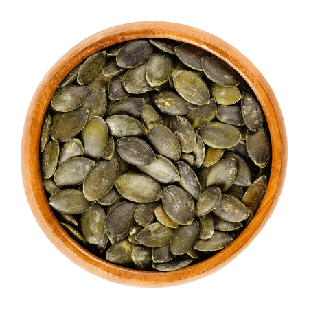 Roasted and salted pepita pumpkin seeds in wooden bowl, used as snack. Flat green edible summer squash seeds of Cucurbita pepo. Isolated macro food photo close up from above on white background.
